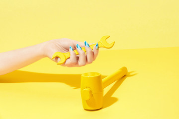 Nails Design. Hand With Colorful Nails On Yellow Background