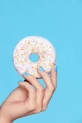 Manicure. Hand With Blue Nails Holding Donut
