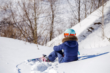 Image from back of athlete in helmet sitting on snowy slope