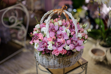Beautiful white vintage basket of pink orchids and roses