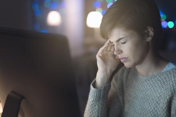 Woman having an headache late at night