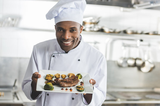 happy african american chef holding plate with cooked steak and vegetables at restaurant kitchen