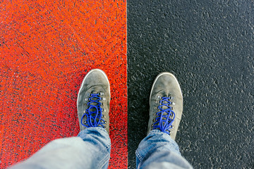 Concept of facing a crucial decision shown by shoes on different colored pathways