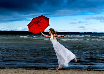 Mary Poppins, modern fashion concept. Caucasian white female model standing with red umbrella and enjoying weather. Beautiful woman with long hair, in a white dress resting in nature.