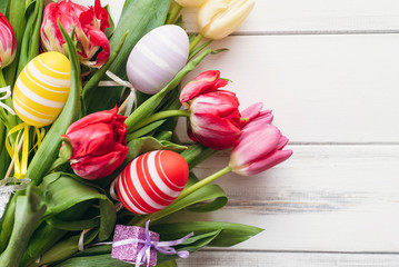 Multicolored eggs and tulips with a gift for Easter on a white background. View from above and copy space