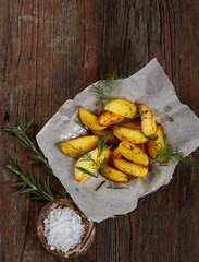 Fried Country-style Potato wedges and salt on wooden backgro