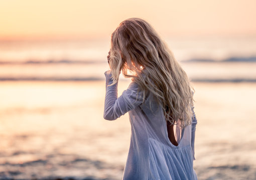 Beautiful blonde girl with long hair in short white dress walking at sunset on the beach in Bali, Indonesia touching hair