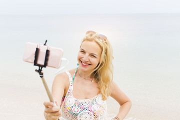 young, blond beautiful woman doing selfie photo with her smartphone on a great beach in thailand