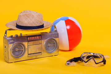 tape recorder, hat, beach ball and snorkel with scuba mask isolated on yellow
