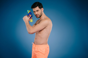 handsome young man in shorts holding water gun and looking at camera on blue