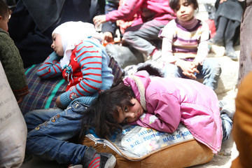 A girl looks at the camera during evacuations from the besieged town of Douma