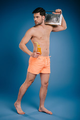 young barefoot man in shorts holding tape recorder and glass of summer cocktail on blue