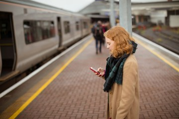 Young woman standing on railway platform using her mobile phone
