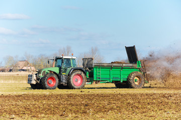 Tractor with manure spreader on the field - 1303