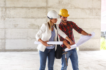 Female inspector and architect discuss with head engineer about blueprints on construction site.