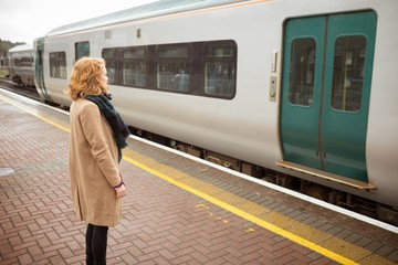 Young woman standing on platform in front of running train