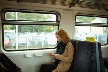 Red hair young woman using smartphone in train