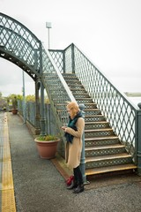 Woman using mobile phone at railway station