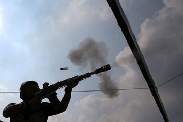 A man shoots at target during a practice session at a shooting range in Bangkok