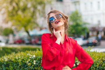 Close-up portrait of gorgeous girl in sunglasses posing to the camera in park. She wears red blouse and nice hairstyle.