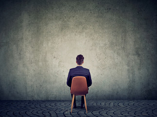 Businessman sitting on chair in front of concrete wall solving a problem