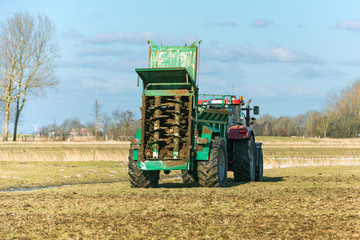 Tractor with manure spreader on the field - 1341
