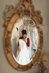 Reflection of bride trying wedding dress from clothes hanger in