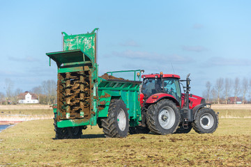 Tractor with manure spreader on the field - 1286