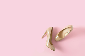 Beige women high heel shoes on pink background. Fashion blog look. Top view, free copy space.
