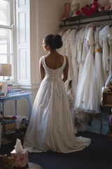 Young bride in white dress looking through the window