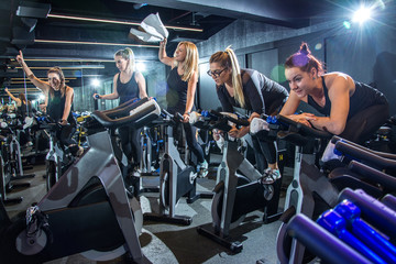 Group of cheerful sporty girls training on fitness bikes and having fun together on cycling class in gym
