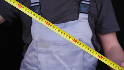 The master, builder or repairman holds in his hand a yellow tape measure of metrics, in a special suit, a black background.