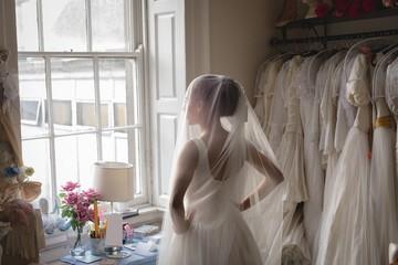 Bride in wedding dress looking through window