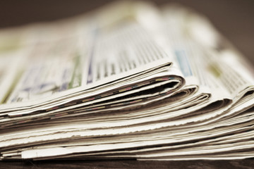 Bunch of newspapers folded and stack in a pile, concept for news. Paper background