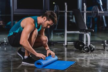 sportsman rolling up yoga mat in sports center