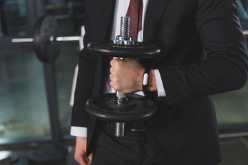cropped view of businessman in suit with fitness tracker holding dumbbell in sports center
