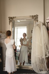 Beautiful young bride in white wedding dress looking into mirror