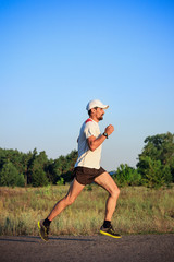 A bearded man running along the road in a cap, t-shirt, shorts, and sneakers.