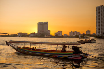 local passenger ship for tourism sailing on river with Thailand building condominium and sunset twilight sky background