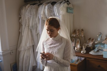 Young bride in wedding dress using mobile phone