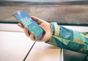 User Holding Smartphone on Moving Train Mockup