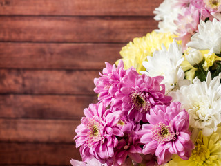 Bouquet of multicolored chrysanthemums on brown wooden background Place for text
