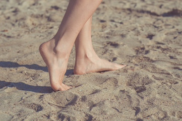 Close up of woman legs walking barefoot on sand in summer holidays on the beach. Vacation concept.