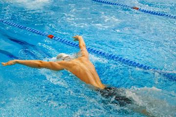 back male athlete swim butterfly stroke in pool splashing water