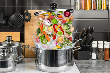 vegetable meat ingredients falling into stainless steel cooking pot creative concept kitchen white induction hob food cooking background