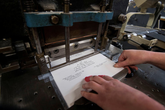 Lottie Small use the die stamping press at the workshop of Barnard and Westwood, who are printing the invitations for Britain's Prince Harry and Meghan Markle's wedding at Windsor Castle in May, London