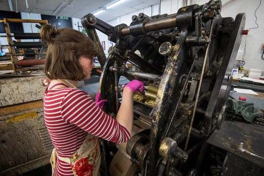 Lottie Small adds gold ink to the die stamping press at the workshop of Barnard and Westwood, who are printing the invitations for Prince Harry and Meghan Markle's wedding at Windsor Castle in May, London