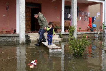 A young child looks on next to a flooded house in Shkodra
