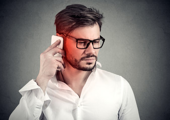 Man on the phone with headache. Upset unhappy guy talking on a cellphone on gray background. Negative emotion face expression