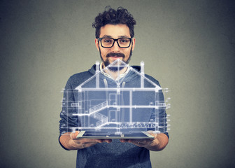 Bearded man in eye glasses using portable electronic pro tablet computer showing new home project